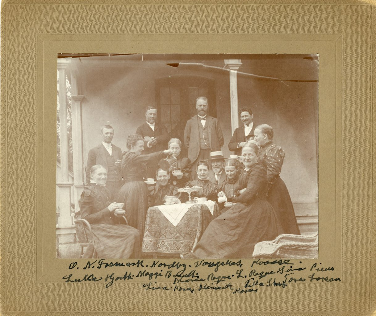 Approximately thirteen adults sit outside around a table drinking coffee.