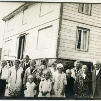 Large group of family nicely dressed outside of home in Roldal, Norway.