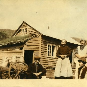 Two women and two men pose for photo outside of house.