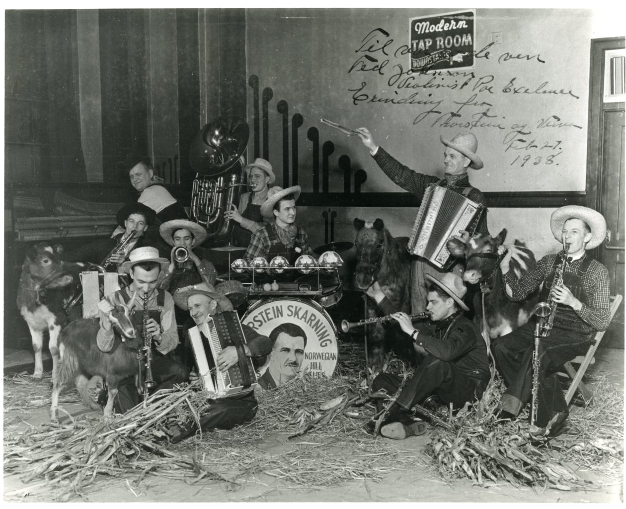 Ten men and farm animals inside playing instruments.