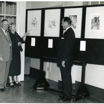 Three individuals look at the Kittelsen exhibit.