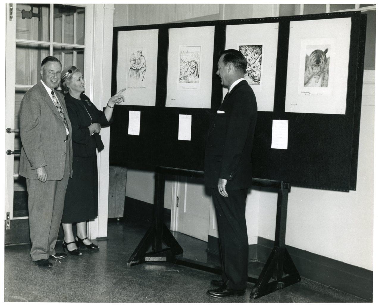 Three individuals look at the Kittelsen exhibit.