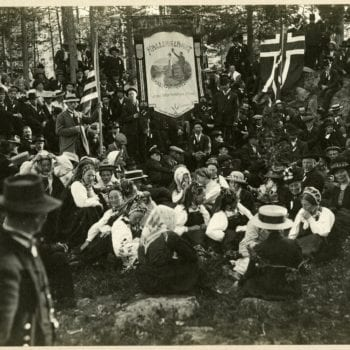 Large group outside in national dress with Norwegian and American flags flying.