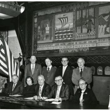 Group of seven men and two women sitting at table.