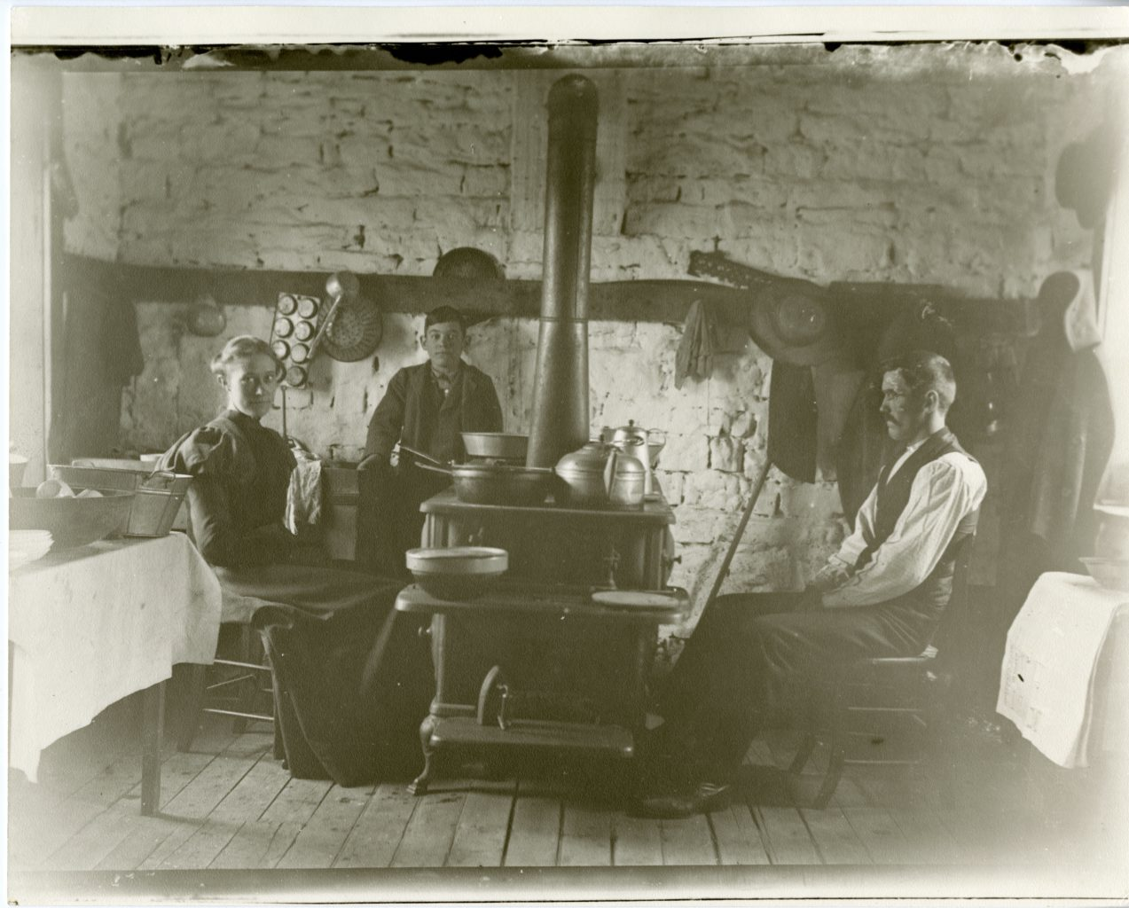 Man, woman, and child sit around stove.