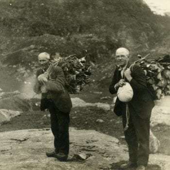 Two men carry sticks.
