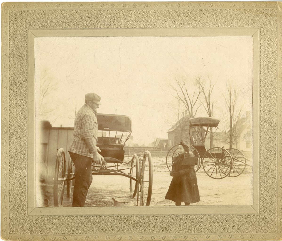 Man and young girl interact. Two buggies in the background.