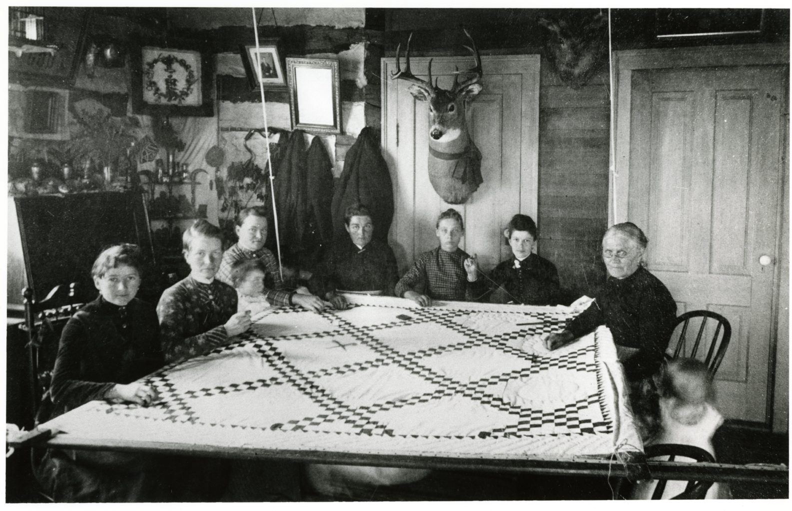 Seven women and two children quilting inside.