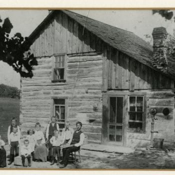 Family poses for photo outside of home.