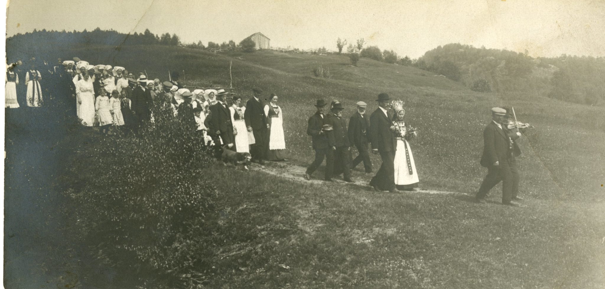 Large group of people parade down a dirt road during a wedding.