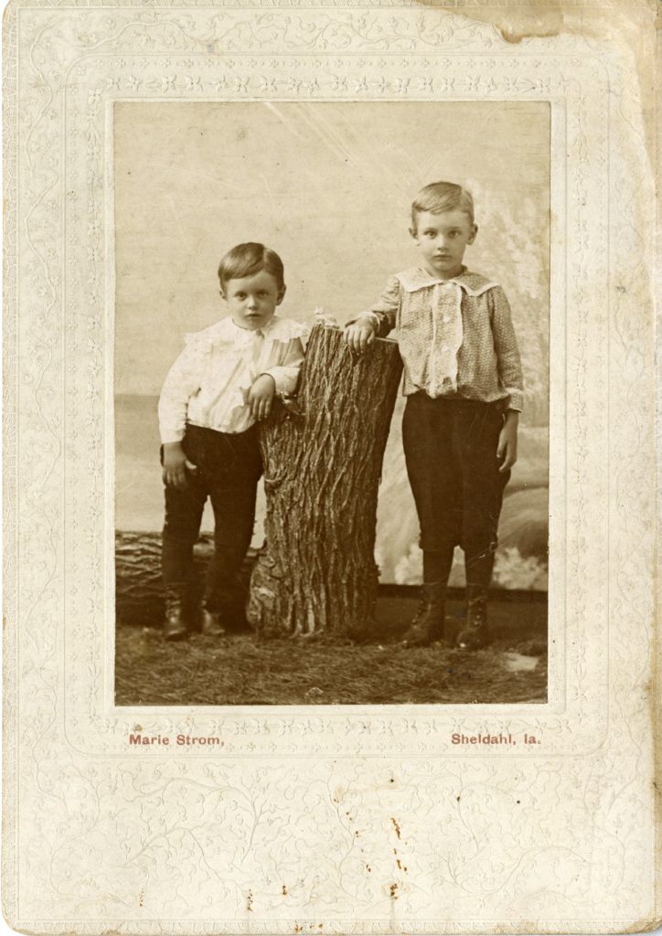 Two boys pose next to a tree stump in a studio.