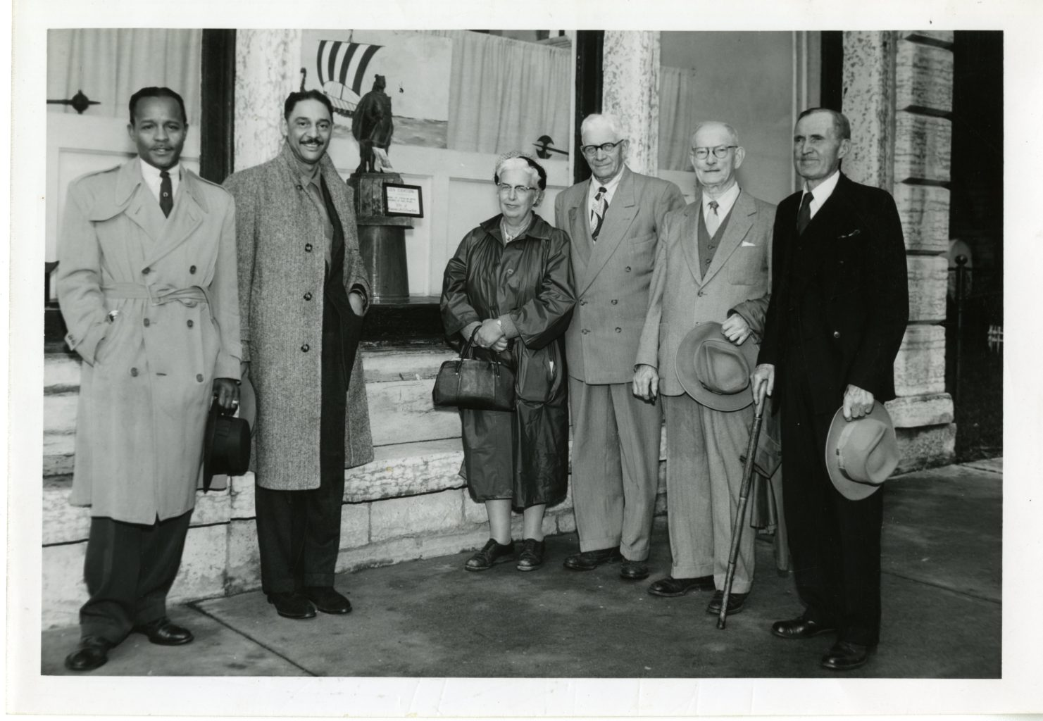 Group of five men and woman posing for a photo outside of a building.