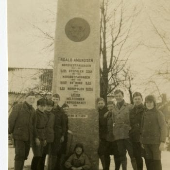 A group of young men pose for a photo next to Roald Amundsen's monument.