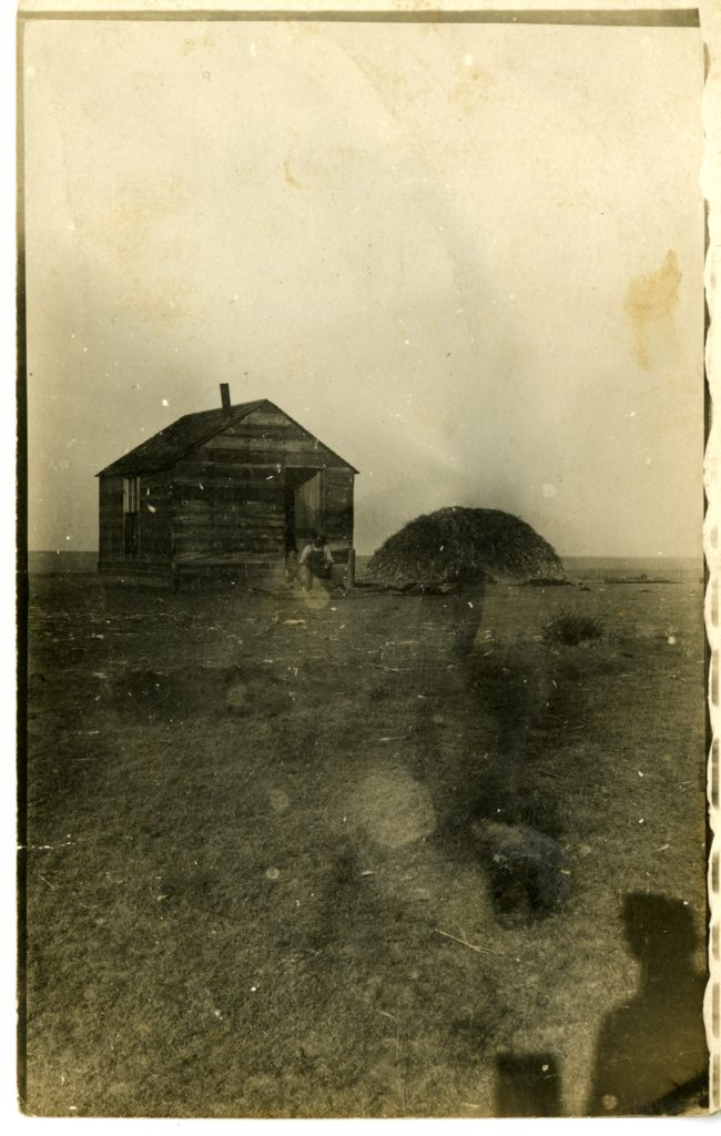 A house in the middle of a field, man and child stand in doorway.