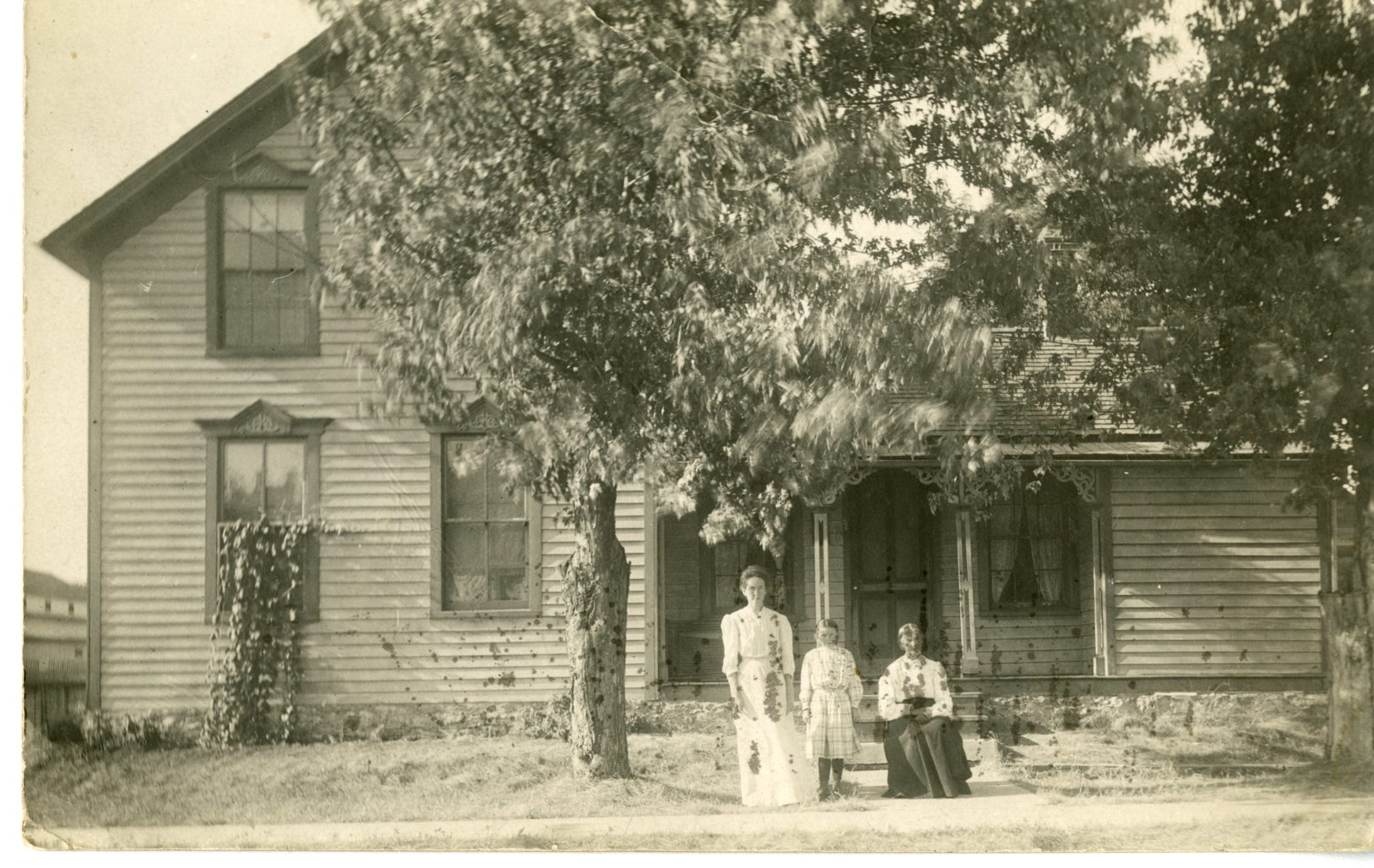Three women pose for a photograph outside a house.