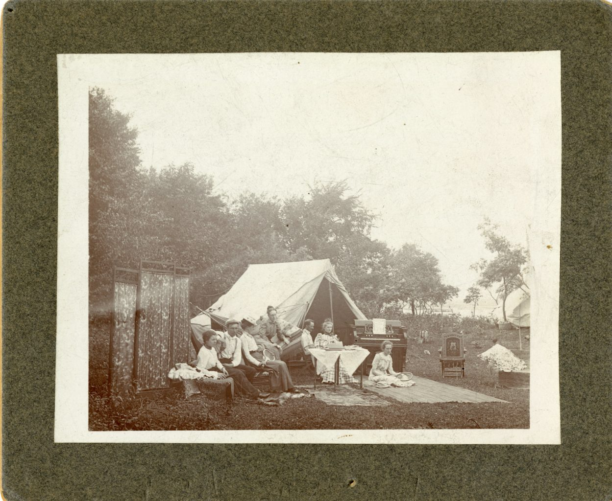 Five women and two men sit outside with tent and rugs. Some holding rackets.
