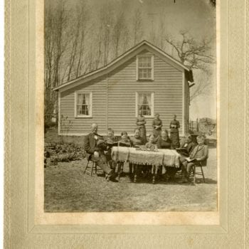 A man and seven children sit around a table outside and read. Three women stand behind and house in background.