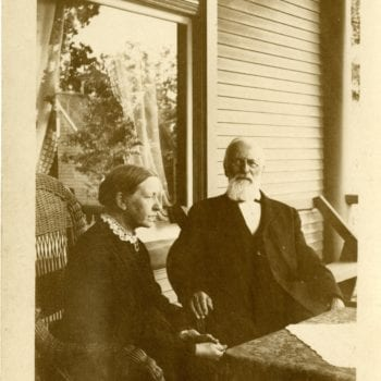 A man and woman sitting in chairs on porch.