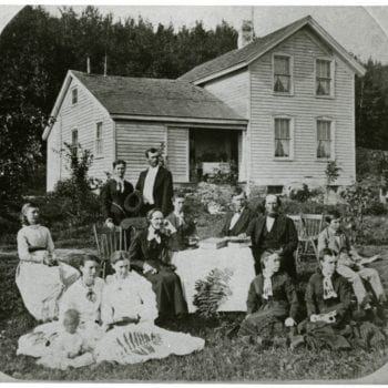 A family sits outside with books.