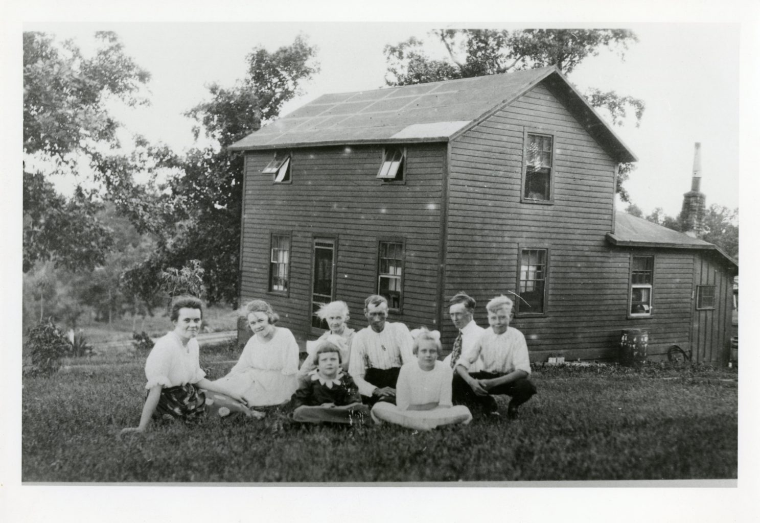 A small family sits outside of their house on the ground.