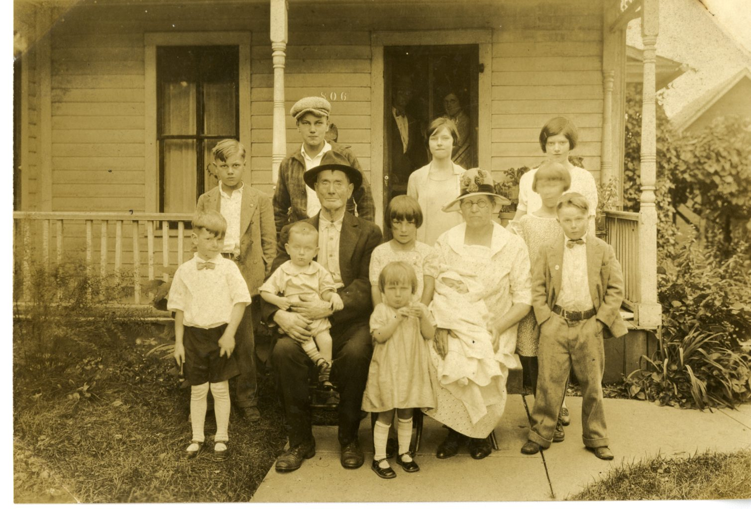 Grandparents and grandchildren pose for a photo outside of house.