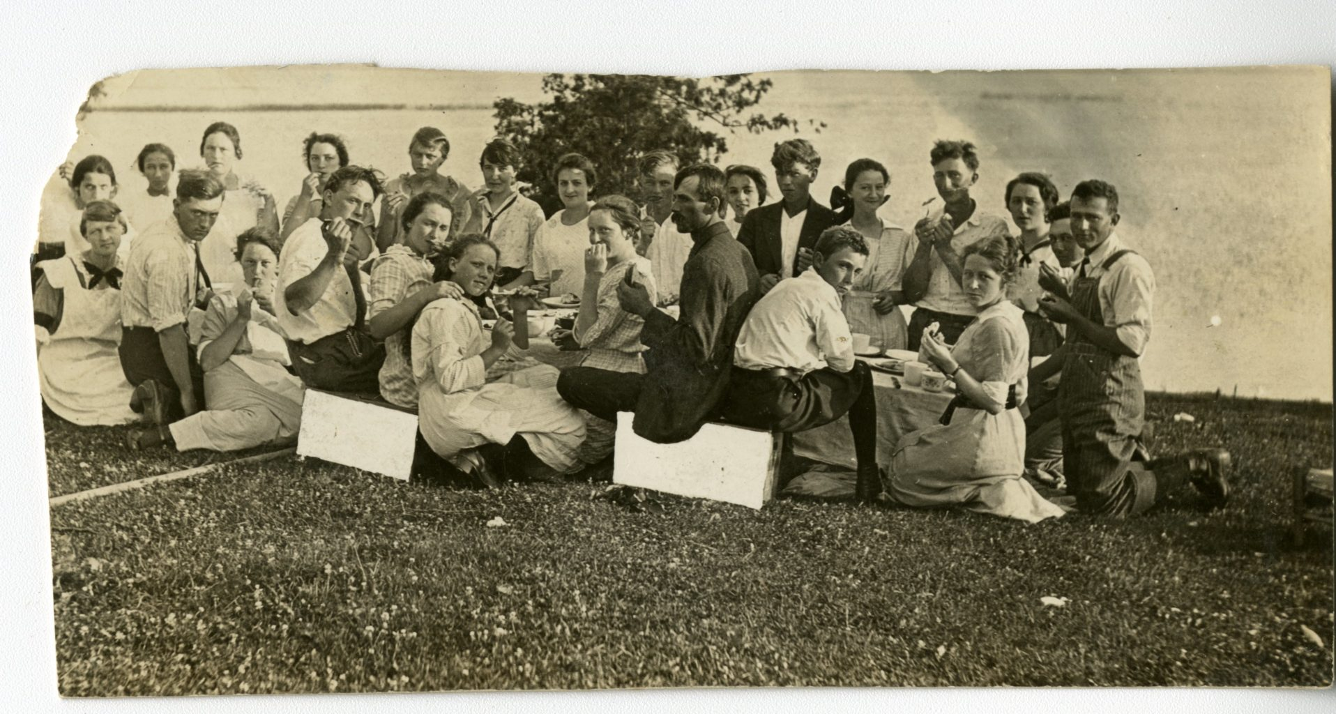 Group of young adults eat around a table outside by the water.