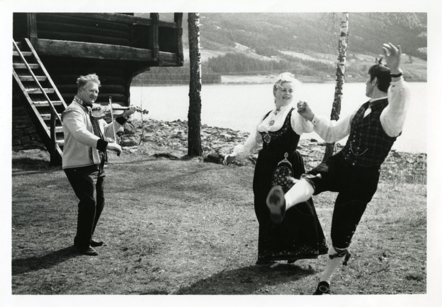 Man and woman dance in Norway with man playing instrument.