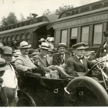 Large group of men, some in car, outside of train.