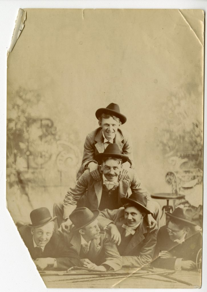 Six men lay on top of each other for photo in studio.