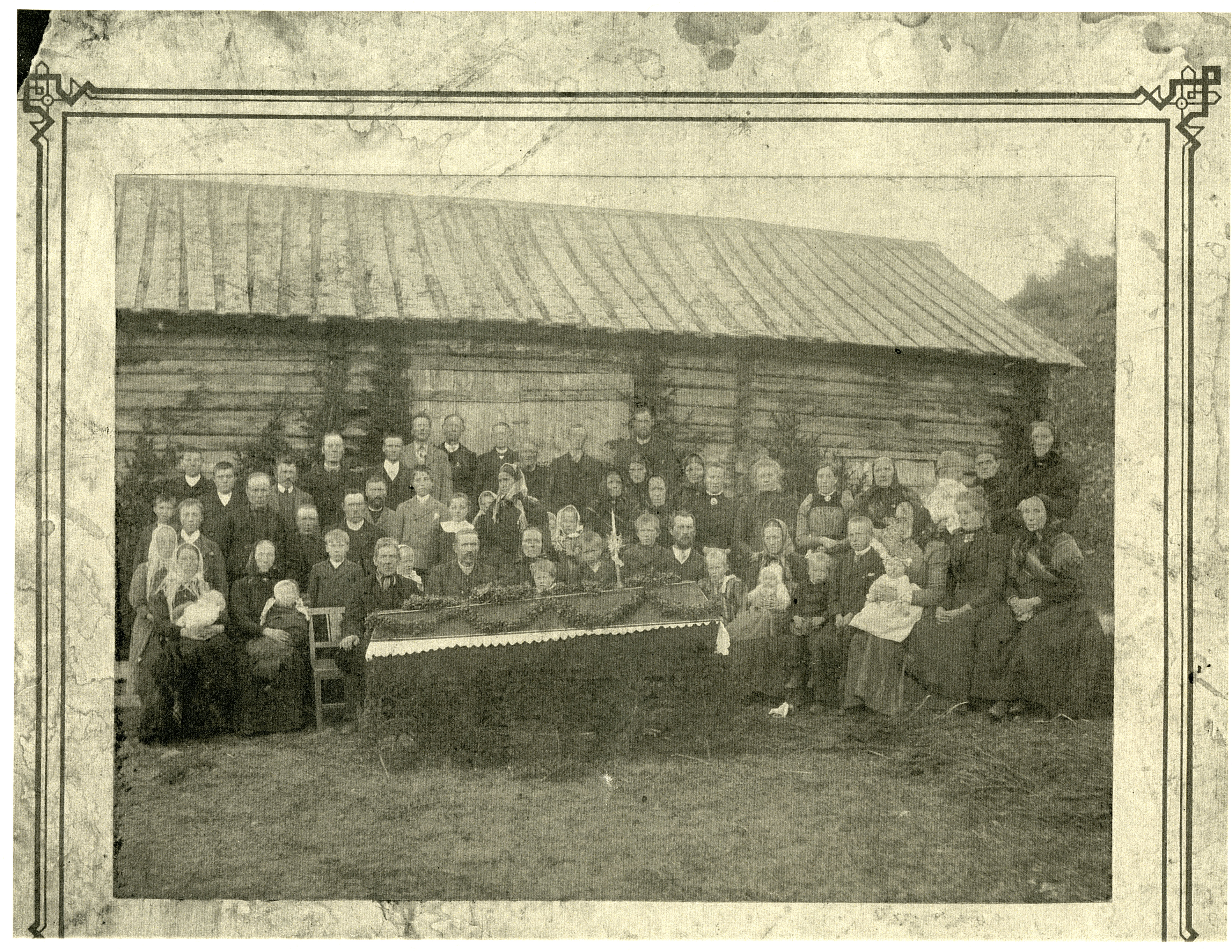 Large gathering of men, women, and children for a funeral.