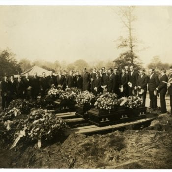 Large group of men and one woman at a funeral for four, who died in a collision.