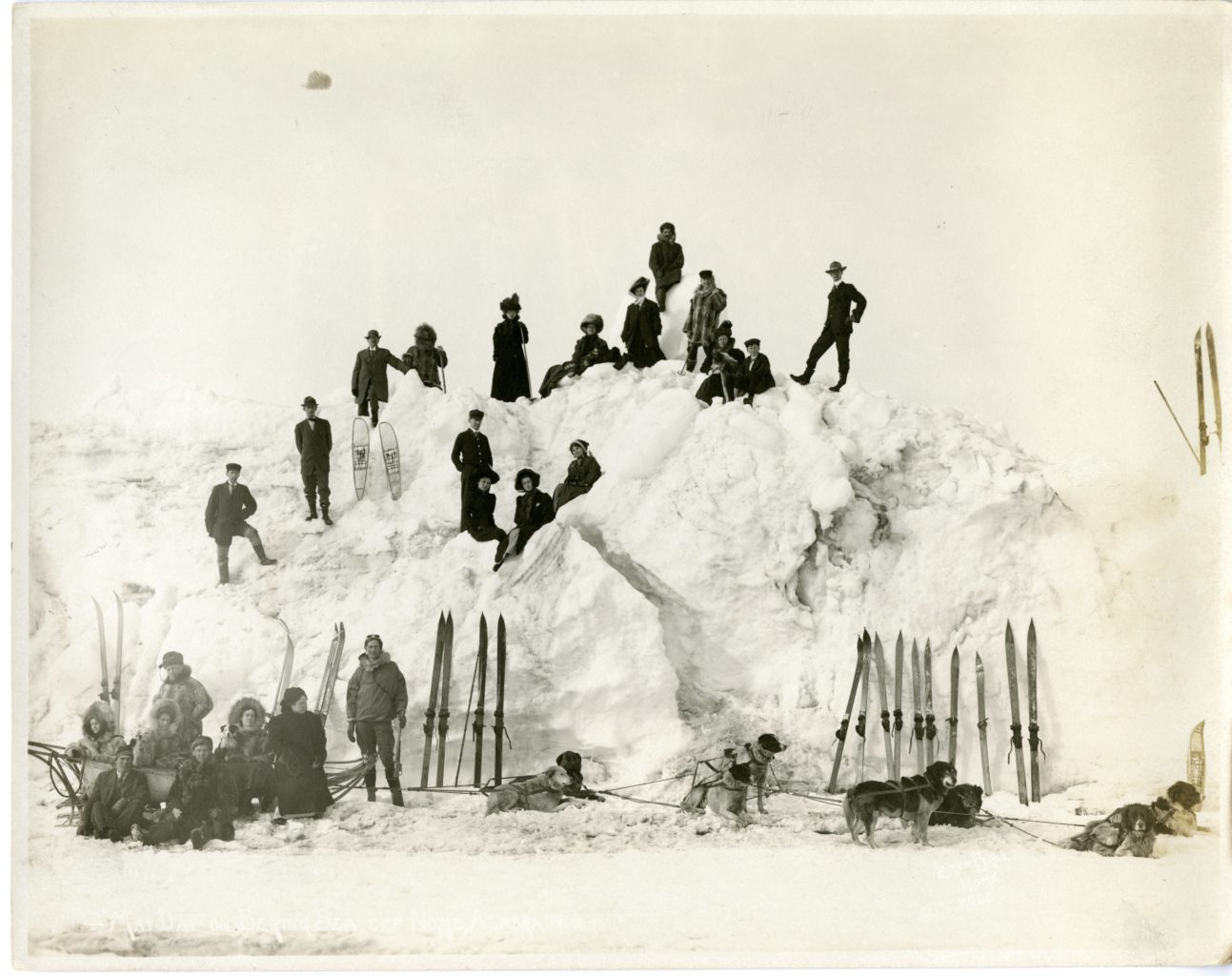 Group with sled dogs pose on snow pile.