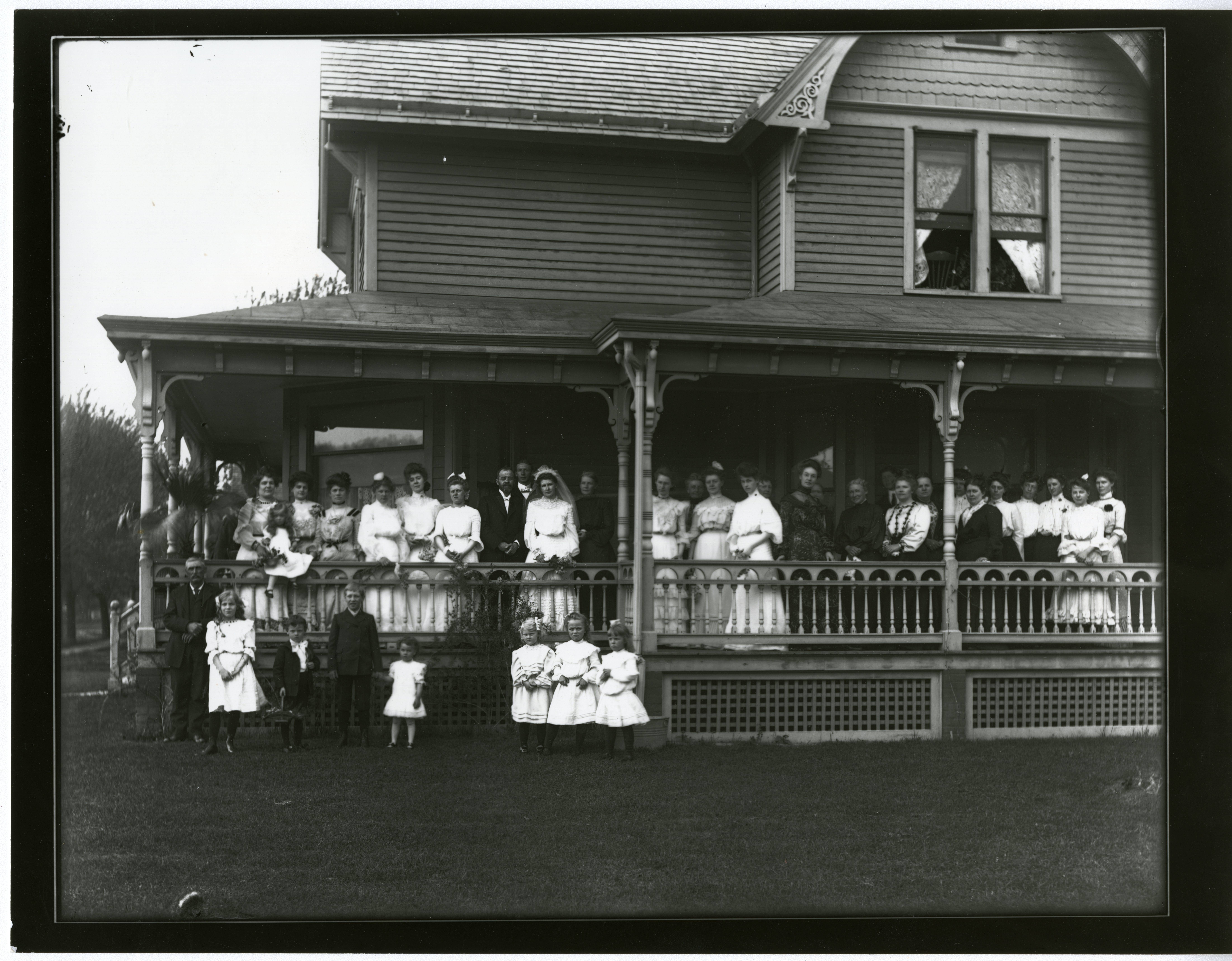 Wedding party poses for photo outside of house.