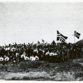 A large crowd of Norwegians in national dress with Norwegian flags flying.