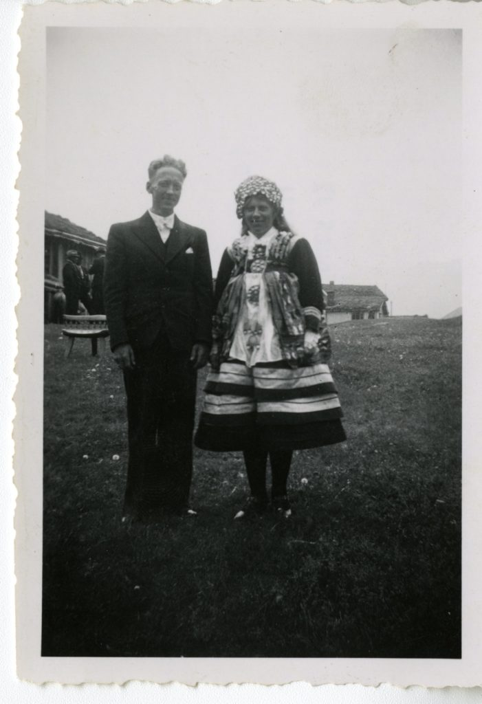 Man and woman pose for photo, woman in national dress.