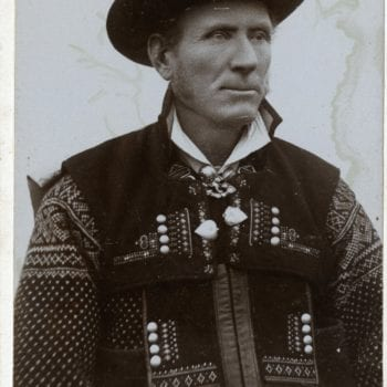 Man poses in studio in national dress and hat.