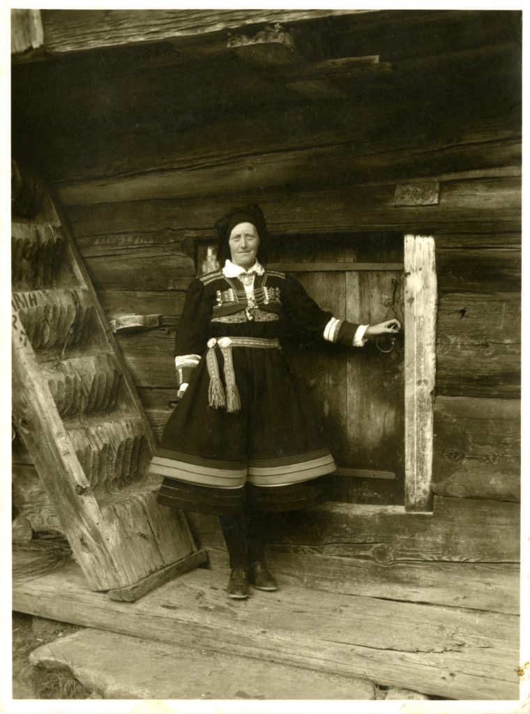 Woman in national dress poses for photo by building.