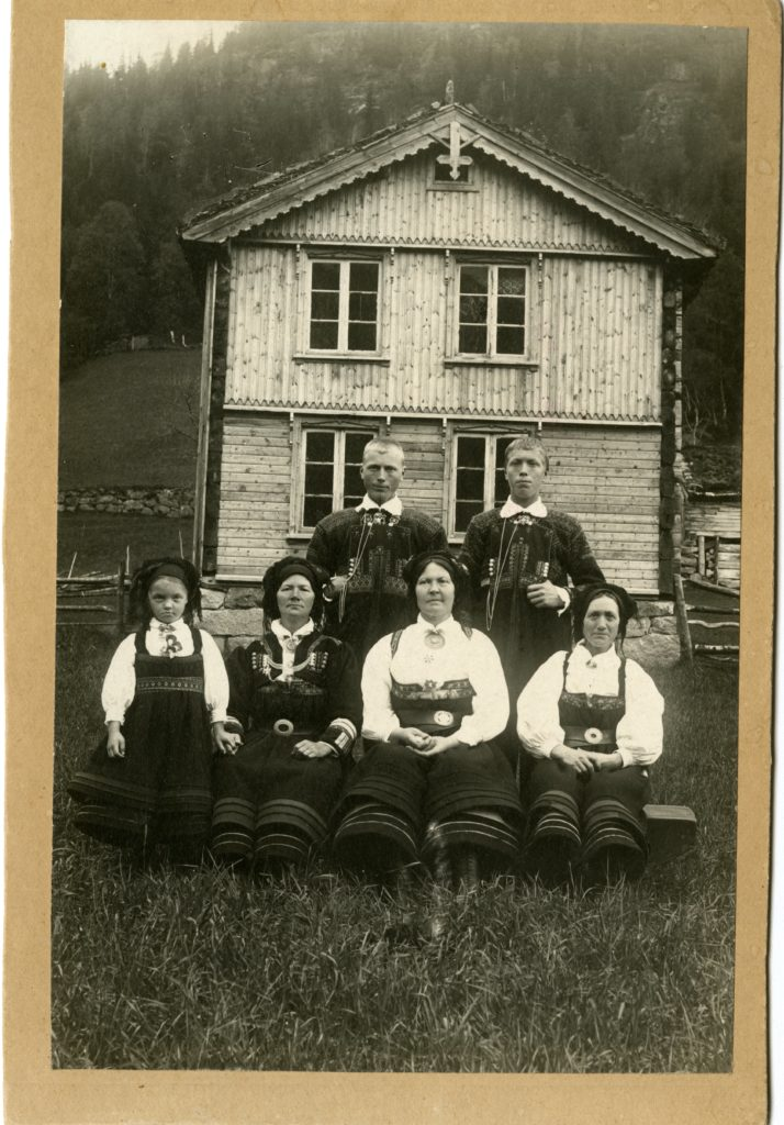 Three women, two men, and one girl in Setesdal dress pose for photo outside of house.