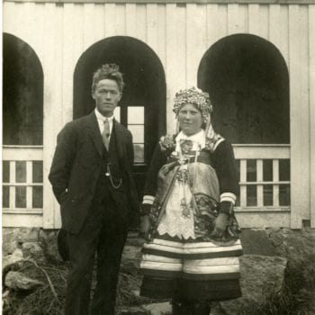 A man and woman pose in front of building. Woman is in traditional Setesdal bunad.