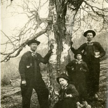 Two men and two boys stand by the largest Bjork tree in Valle, Setesdal.