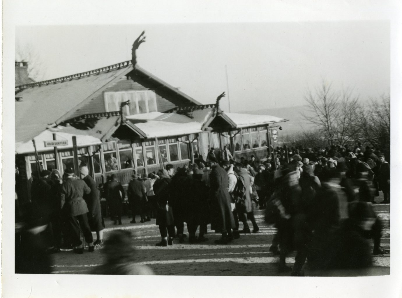 A large crowd gathers outside of building.