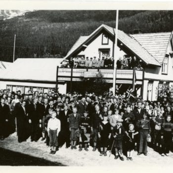 A large crowd poses for a photo outside of building.