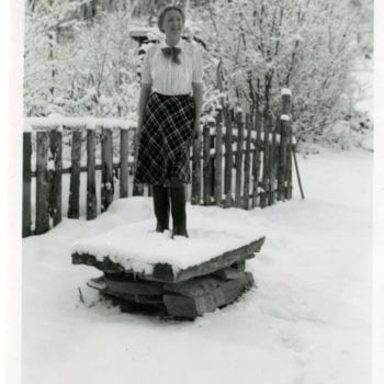 A woman standing on a wood pile in winter.