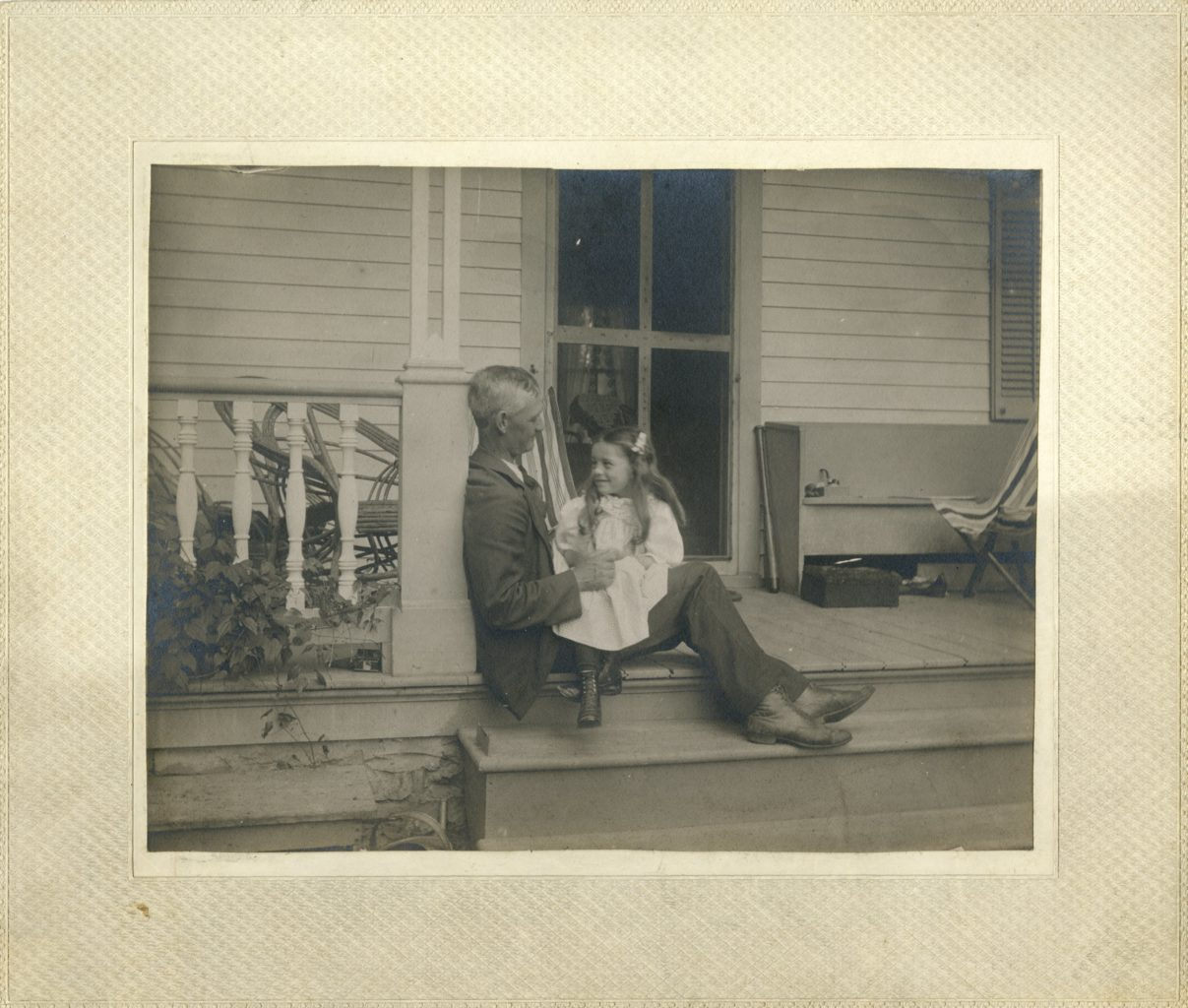 Paul Koren and Esther Torrison sit together on a porch.