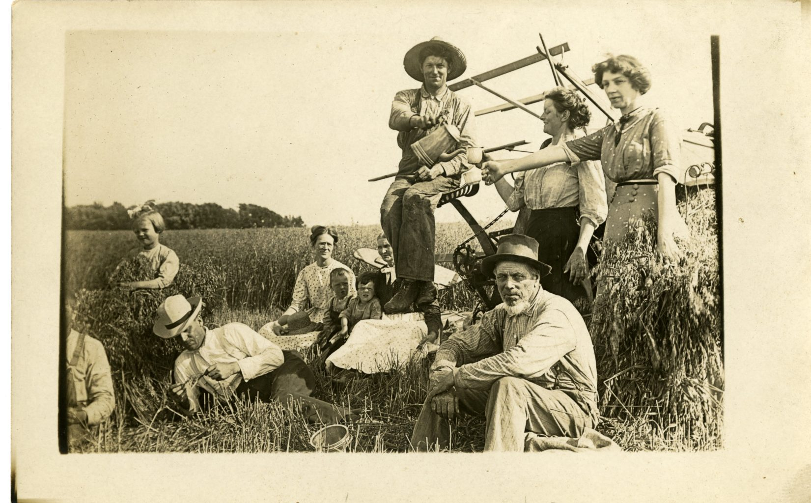 Group of men, women, and children sit in a field, rest from work.