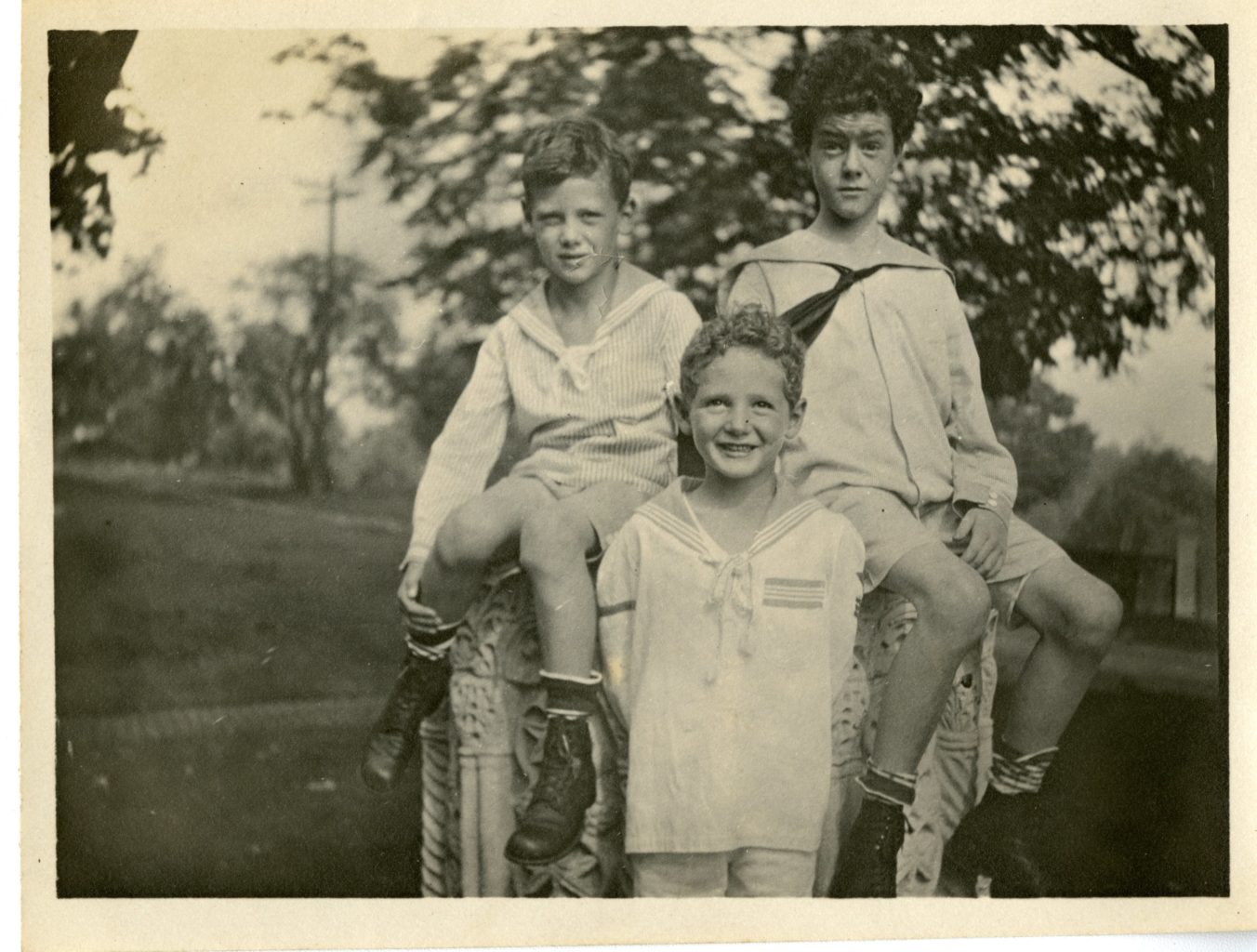 Three boys pose for a photo, two sitting and one standing. All in white.