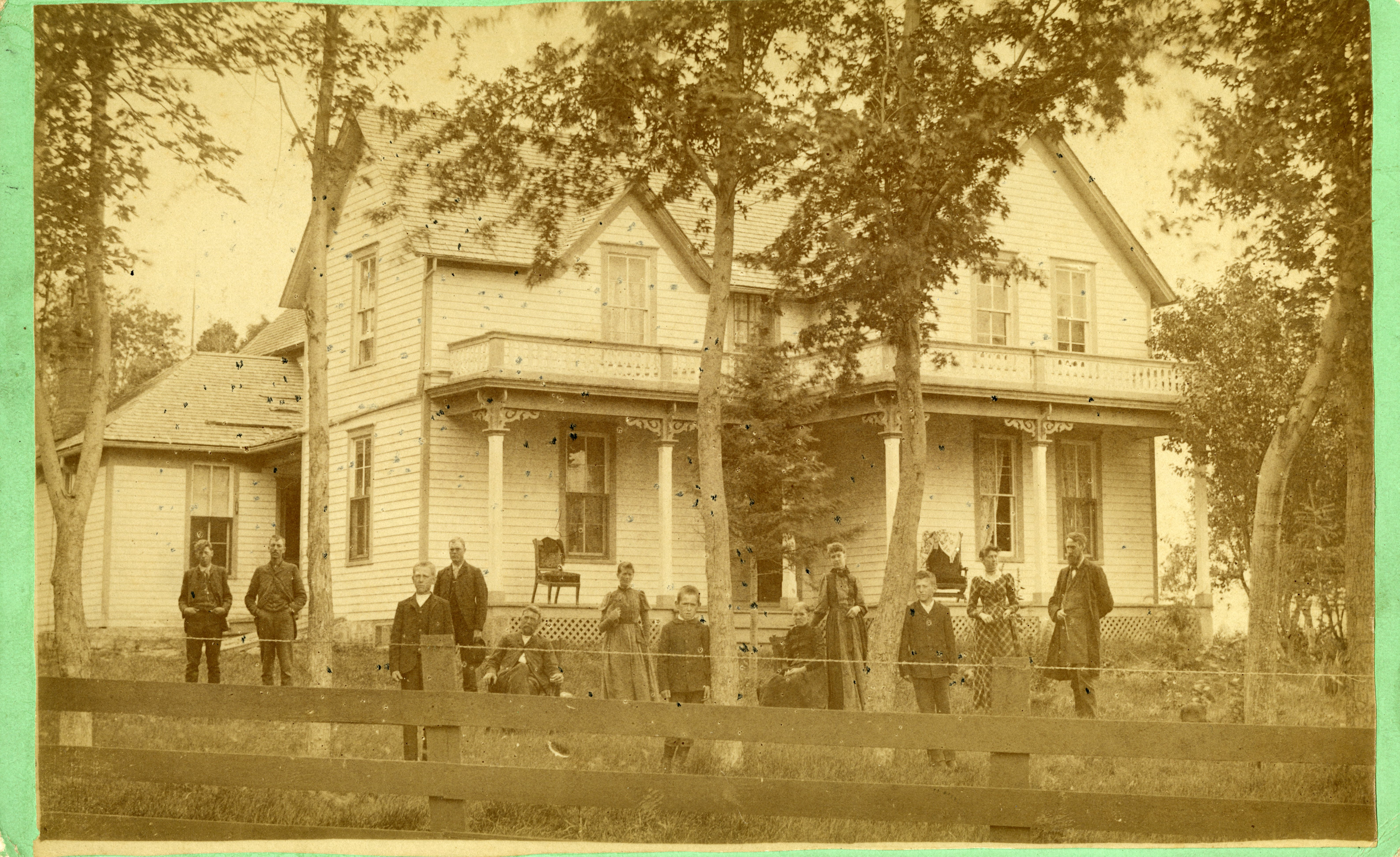 Twelve people stand outside of a house.