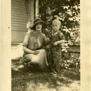 Woman and child pose for a photo outside of house.