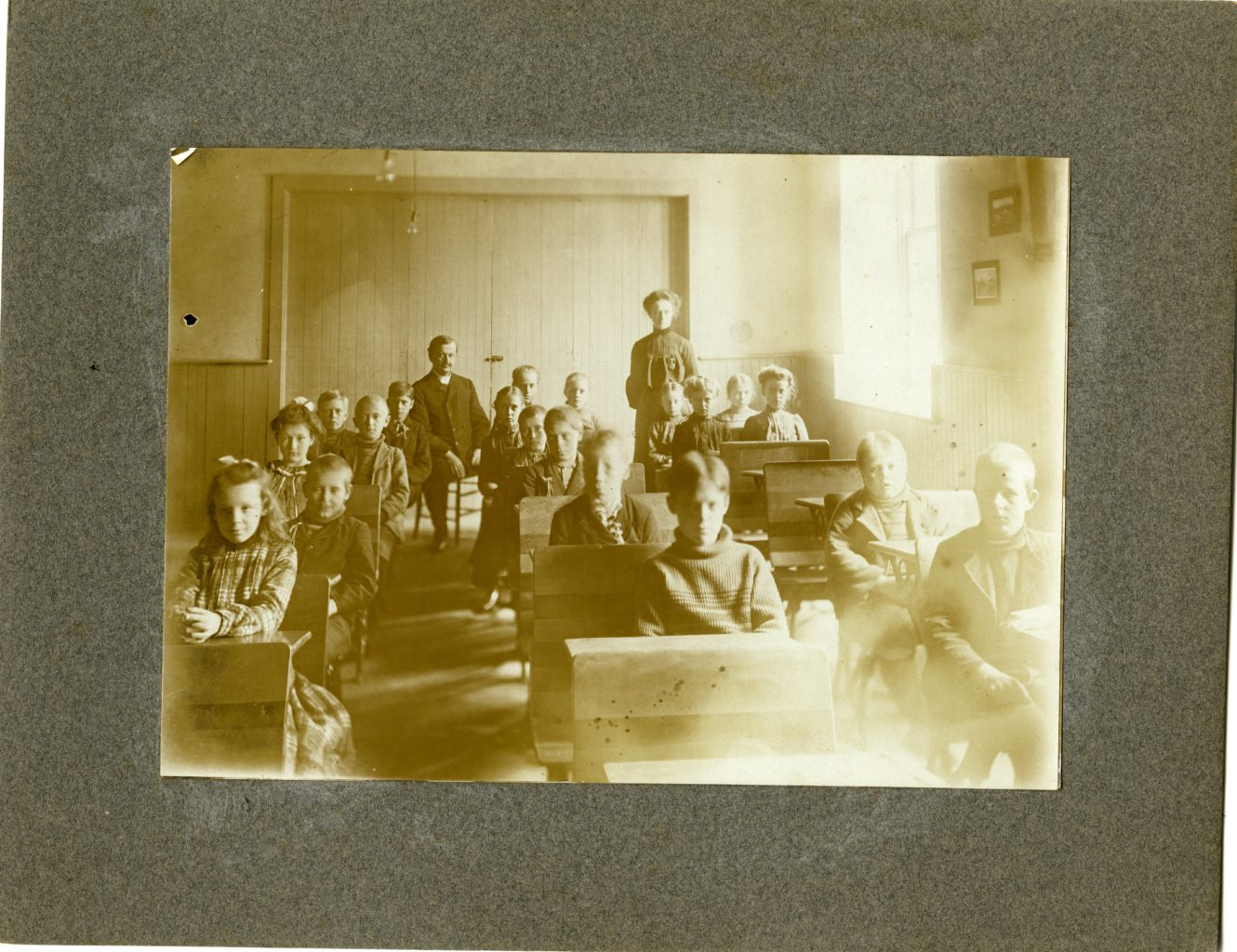 Eighteen children and three adults in a classroom.