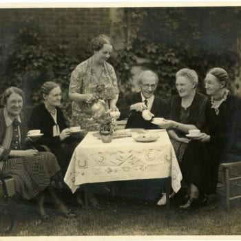 Five women and on man gather for tea outside around a table.